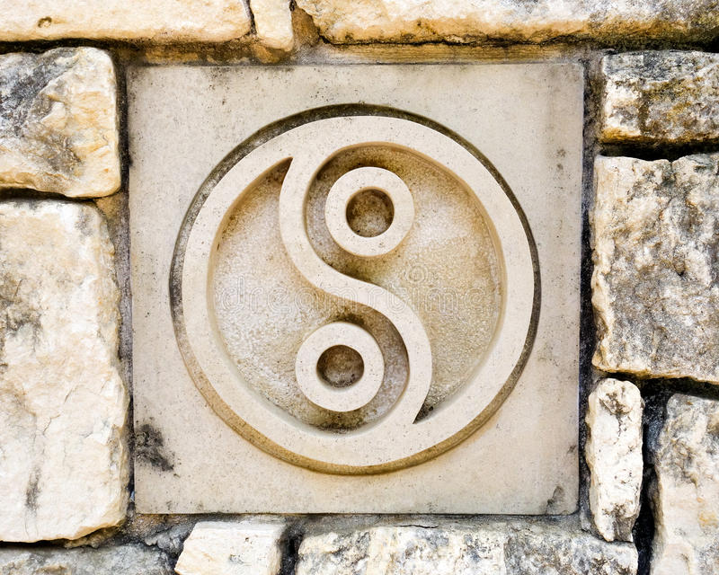 Yin and Yang spiritual symbol. Ceramic tile in old rock wall with yin and yang symbol, representing Tao or taoism, a Chinese religion. Tile is one of a series of royalty free stock photography