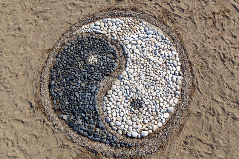 Yin and yang of stones. The conception of yin and yang is laid with stones on the sand,Yin and yang of stones stock image