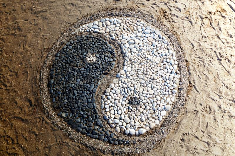 Yin and yang of stones. The conception of yin and yang is laid with stones on the sand,Yin and yang of stones stock images