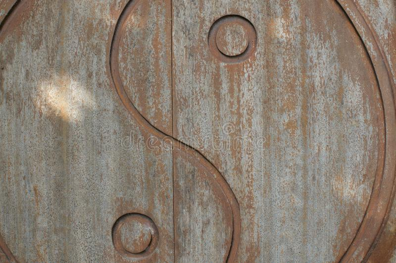 Yin-Yang symbol carved on wooden door stock photo