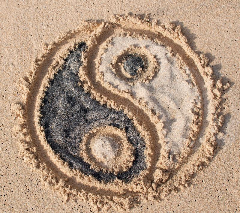 Ying Yang symbol drawn on the beach royalty free stock photos