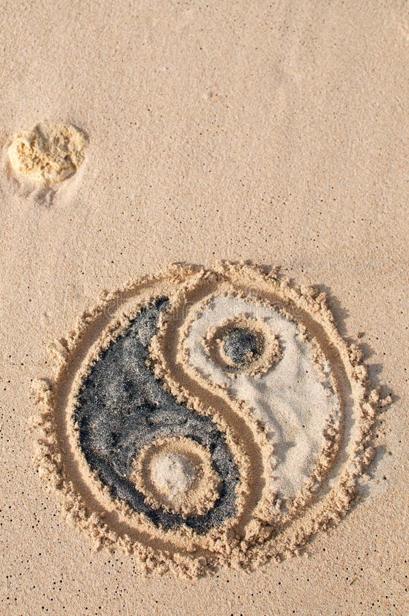 Ying Yang symbol drawn on the beach royalty free stock image