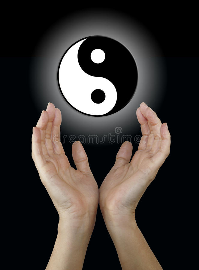 Yin and Yang Symbol. Female hands reaching up towards a floating black and white yin yang symbol on a black background stock photo