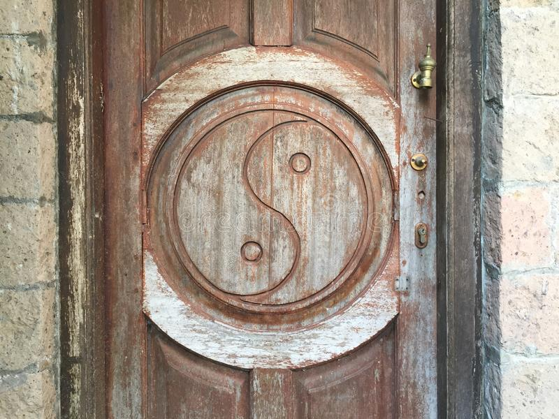 Yin-Yang-Symbol geschnitzt auf Holzt?r lizenzfreie stockbilder