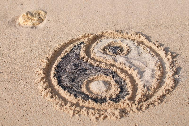 Ying Yang symbol drawn on the beach. Yin-yang symbol drawn and filled with black and white sand at Melasti beach in Bali, Indonesia stock photography