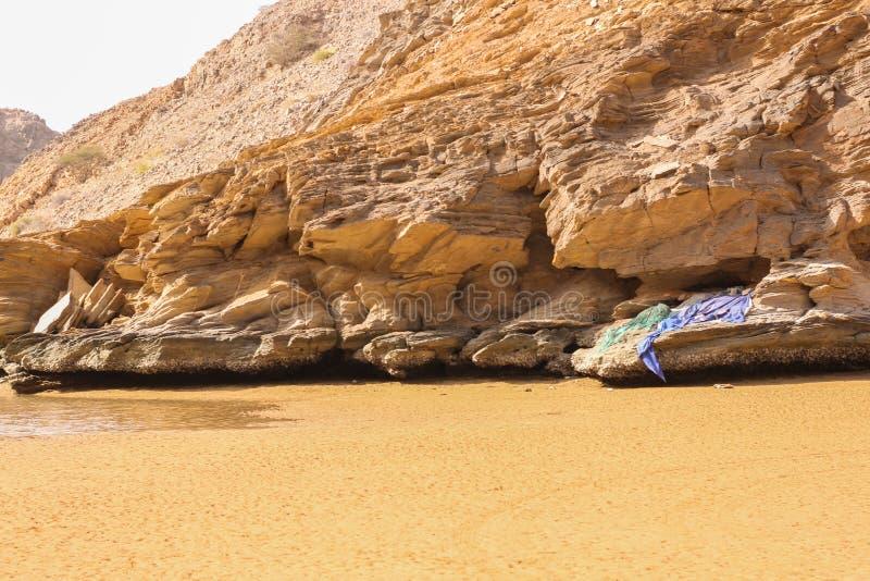 Yiti Muscat Oman strand på en solig dag med det molniga vädret som har berg på bakgrunden fotografering för bildbyråer