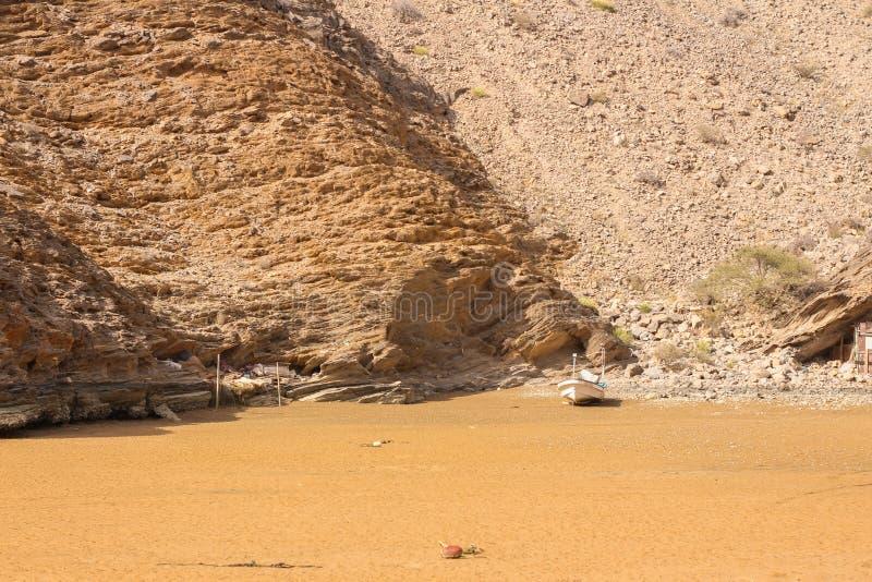 Yiti Muscat Oman strand på en solig dag med det molniga vädret som har berg på bakgrunden arkivfoto