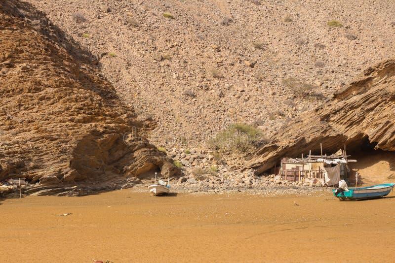 Yiti Muscat Oman strand på en solig dag med det molniga vädret som har berg på bakgrunden royaltyfri bild