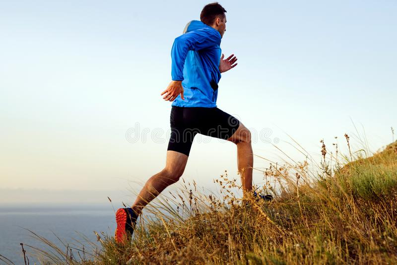 Ynamic running uphill male athlete. Dynamic running uphill male athlete runner in background of sea and sky royalty free stock image