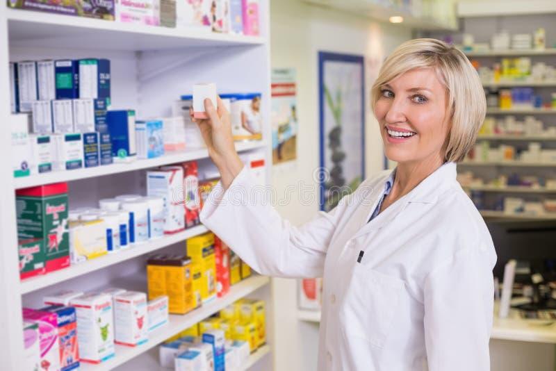 Yngre apotekare som tar medicin från hylla arkivbild