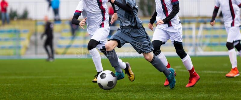 Yngre fotbollsmatch Fotbolllek för ungdomspelare Pojkar som spelar fotbollsmatchen på fotbollgraden arkivfoto