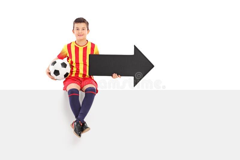 Yngre idrottsman nen som rymmer en pil och en fotboll royaltyfria bilder