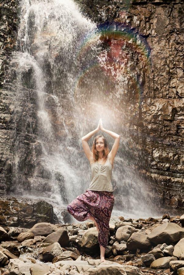 Yogaövning på vattenfallbakgrunden arkivbild