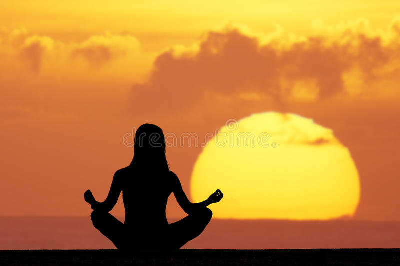 Yoga. Woman doing yoga at sunset royalty free stock image