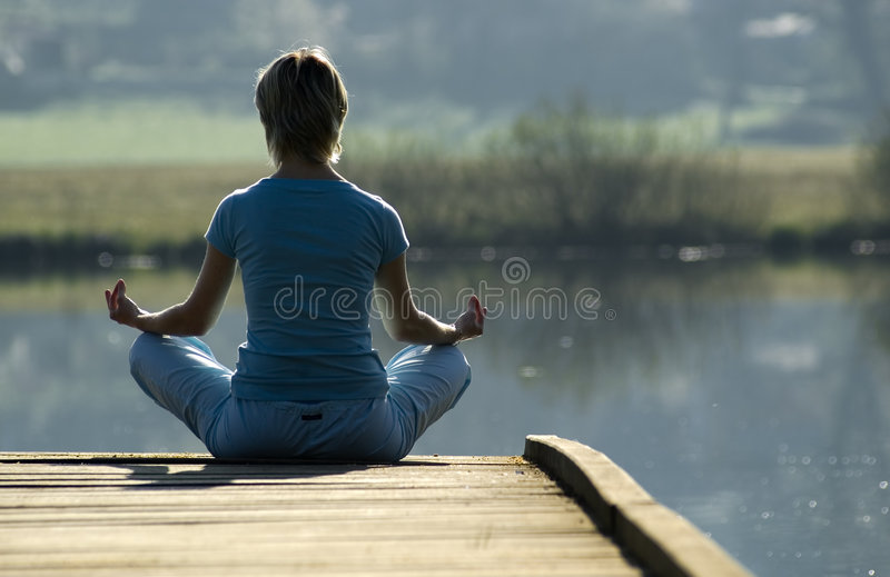Yoga. Young girl relaxing on pier in early morning