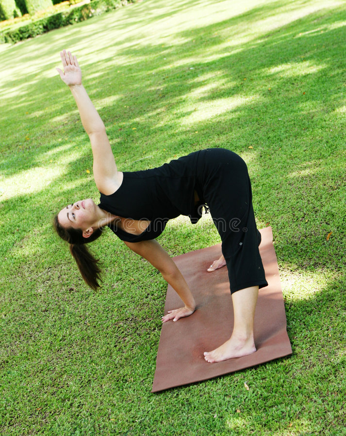 Yoga. Young woman practicing yoga in the park royalty free stock photos