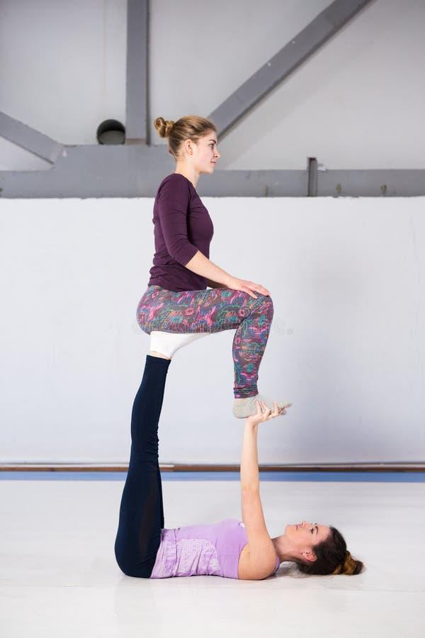 Yoga acrobática de la salud de los deportes del tema Un par de dos muchachas caucásicas jovenes en el gimnasio que hace una silla foto de archivo