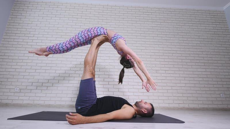 Yoga acrobática Mujer joven y hombre que realizan ejercicios La combinación de la acrobacia y de yoga foto de archivo