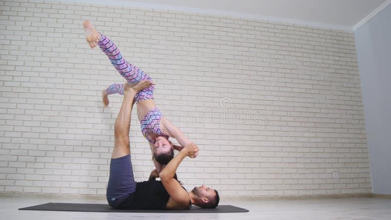 Yoga acrobatique Jeune femme et homme exécutant des exercices La combinaison des acrobaties et du yoga photos stock