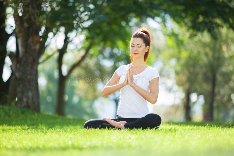 Yoga al aire libre La mujer feliz que hace ejercicios de la yoga, medita en el parque Meditaci?n de la yoga en naturaleza Concept fotos de archivo libres de regalías