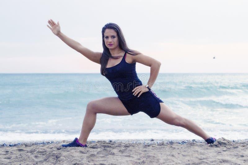 Yoga allant de jeune femme à la plage image libre de droits