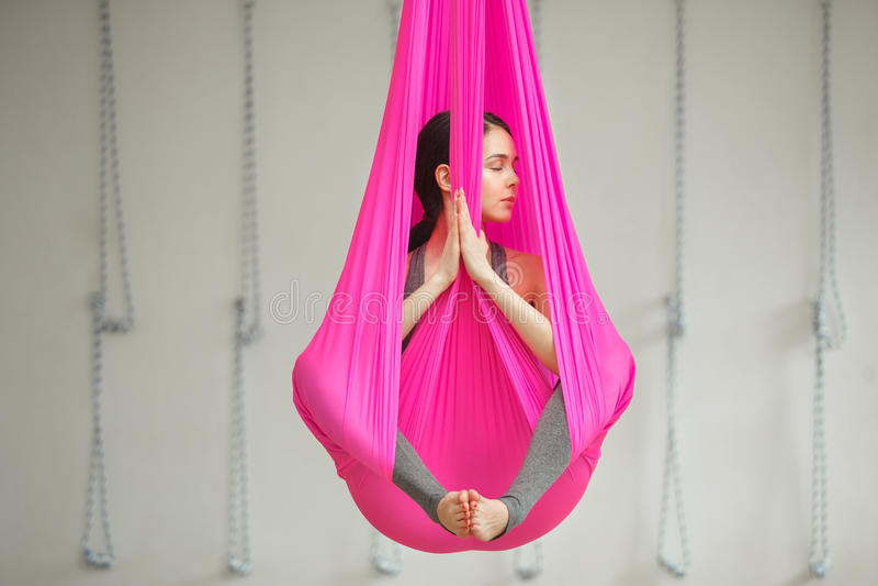 Yoga anti-gravité aérien de pose de lotus de fille La femme s'assied dans l'hamac photographie stock libre de droits