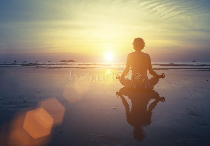 Yoga, aptitud y forma de vida sana Siluetee a la muchacha de la meditación en el fondo del mar y de la puesta del sol imponentes fotos de archivo libres de regalías