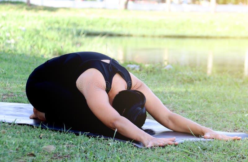 Yoga asiática al aire libre, actitud de la práctica de la mujer del niño fotos de archivo