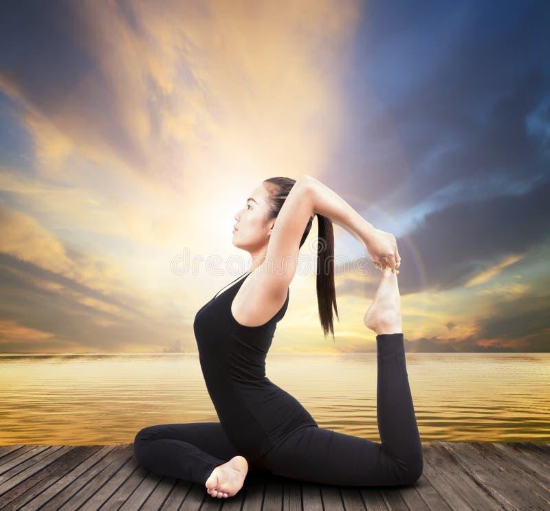 Yoga asiática de la fijación de la mujer de la atención sanitaria hermosa en la terraza de madera imagen de archivo libre de regalías