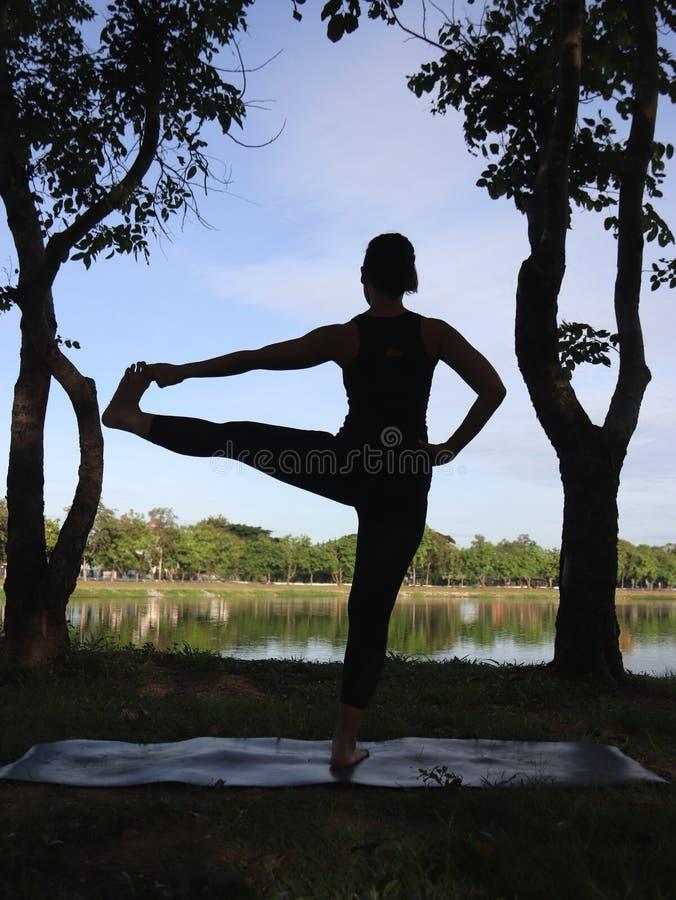 Yoga asiatique de pratique en matière de femme extérieur, main prolongée à la pose de gros orteil, silhouette photographie stock