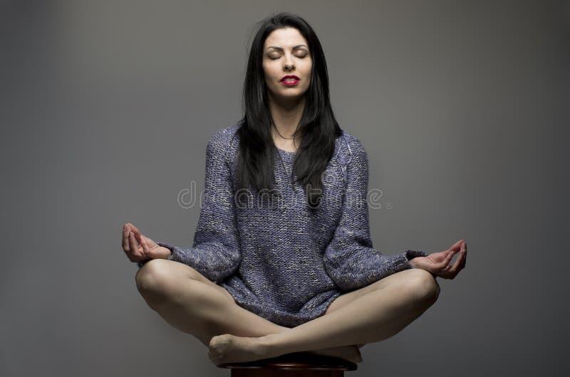 yoga Attraktiv flicka, kvinna med långt sammanträde för svart hår på sto arkivfoton
