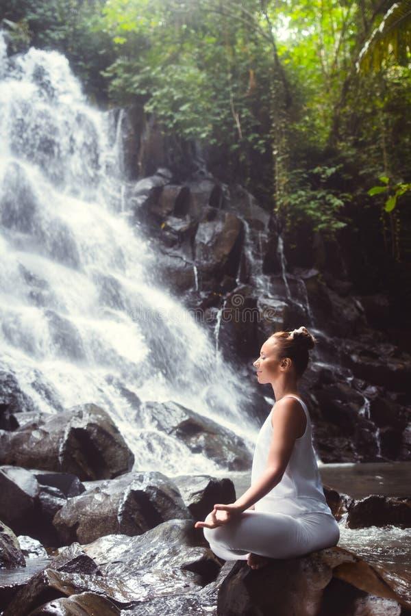 Yoga auf dem Wasserfall lizenzfreie stockfotos