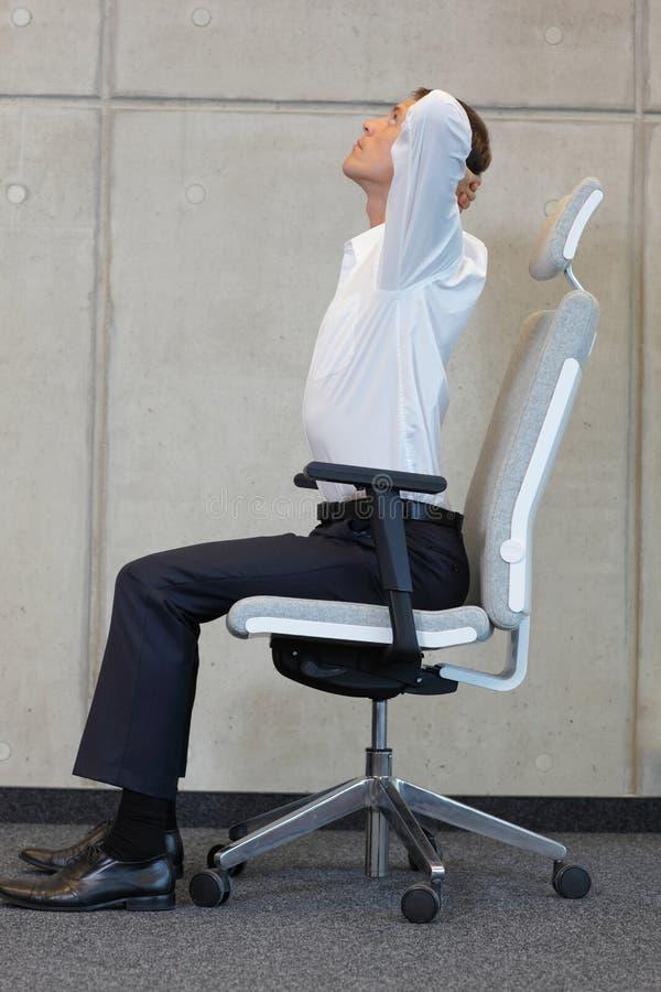 Yoga auf Stuhl im Büro - Geschäftsmanntrainieren stockbild