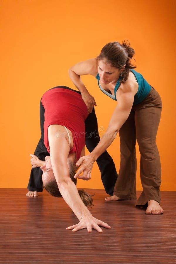 Yoga-Ausbilder-helfender Kursteilnehmer stockfotos