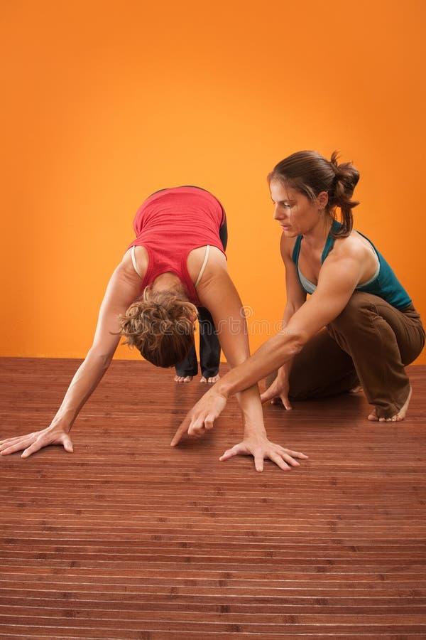 Yoga-Ausbilder hilft ihrem Kursteilnehmer stockbilder