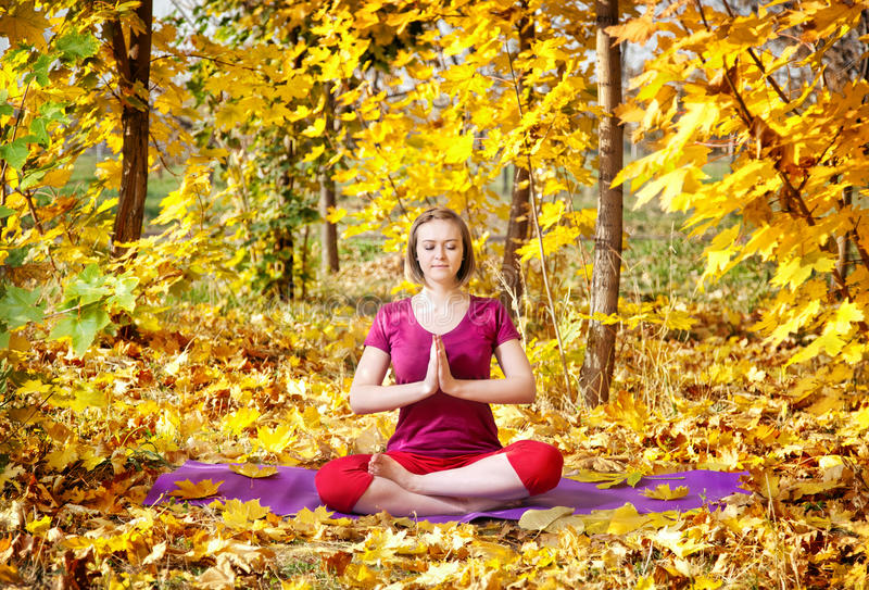 Yoga in autumn. Yoga meditation pose by concentrate beautiful woman in red cloth and yellow leaves around in the autumn stock photography