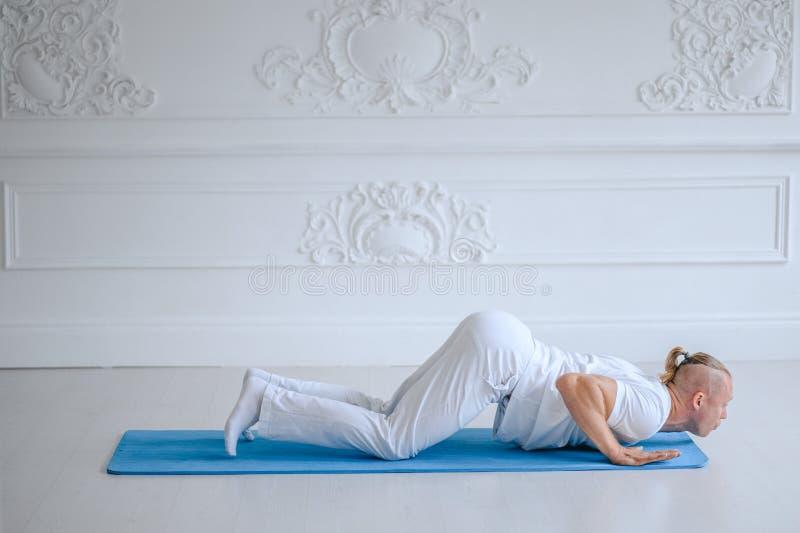 Yoga avanzata di pratica dell'uomo contro un fondo bianco immagini stock