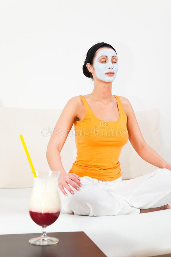 Yoga beauty. Spa and wellness at home woman with facial face mask doing yoga royalty free stock photos
