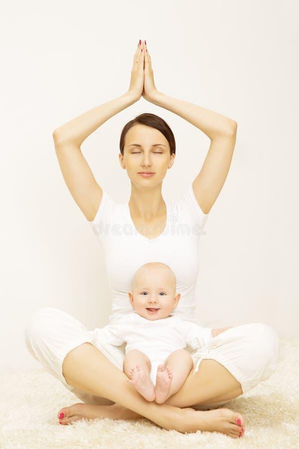 Yoga behandla som ett barn och modern, sportövningen för barnmamman, familj fotografering för bildbyråer
