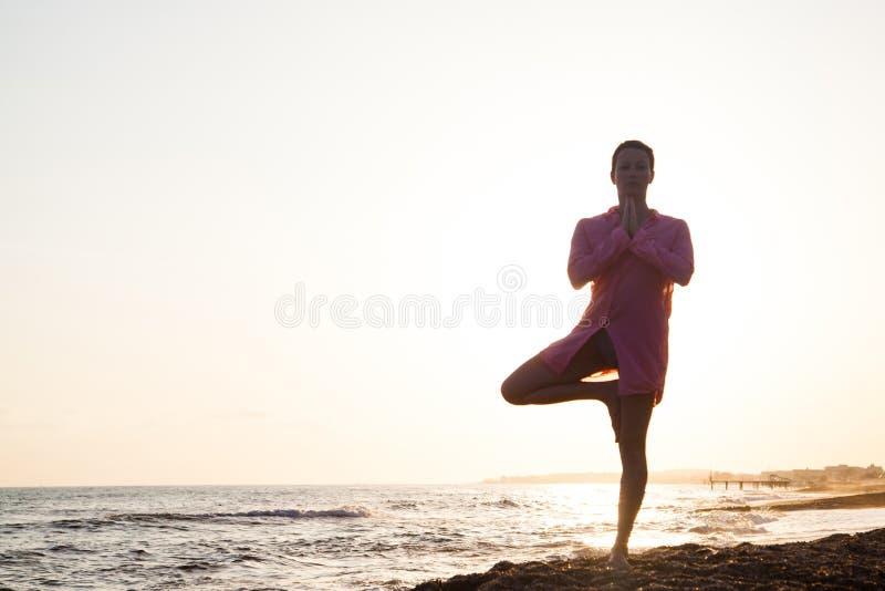 Yoga bei dem Sonnenuntergang stockbild
