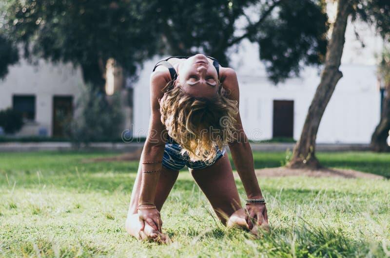 Yoga - bel instructeur mince dehors jeune de yoga de femme faisant l'exercice d'asana d'Ustrasana de pose de chameau dehors photographie stock