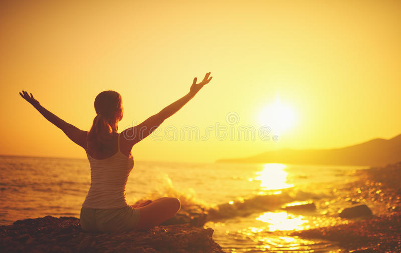 Yoga bij zonsondergang op strand Vrouw die yoga doet