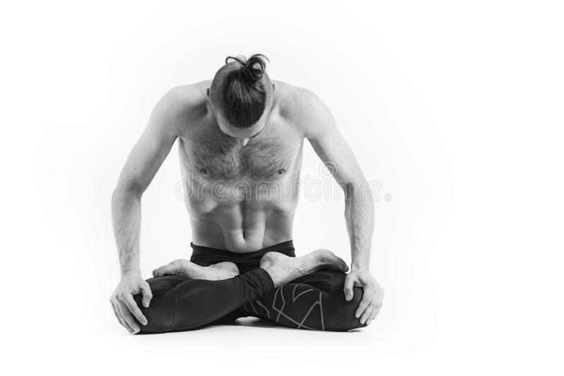 Yoga. Black and white Portrait of yogi men doing yoga exercise, he breath and performing Upward abdominal lock. Young men workout royalty free stock photo