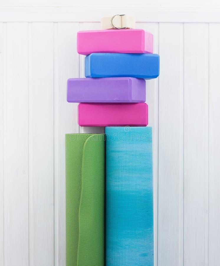 Yoga blocks, strap and carpets. Varicolored iyengar yoga props. Blocks, strap and carpets on woody background royalty free stock photography