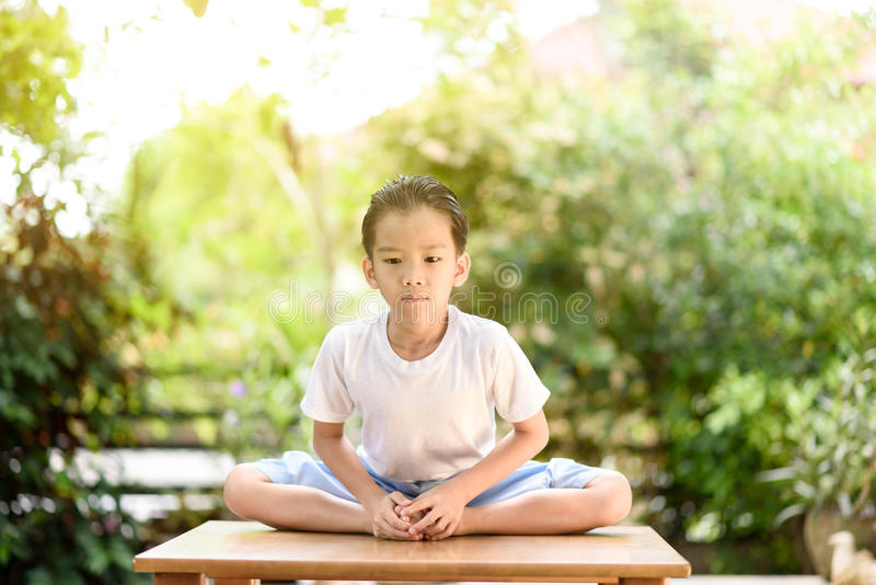 Yoga boy. Young Thai boy practicing yoga in the park.Easy Pose stock photography