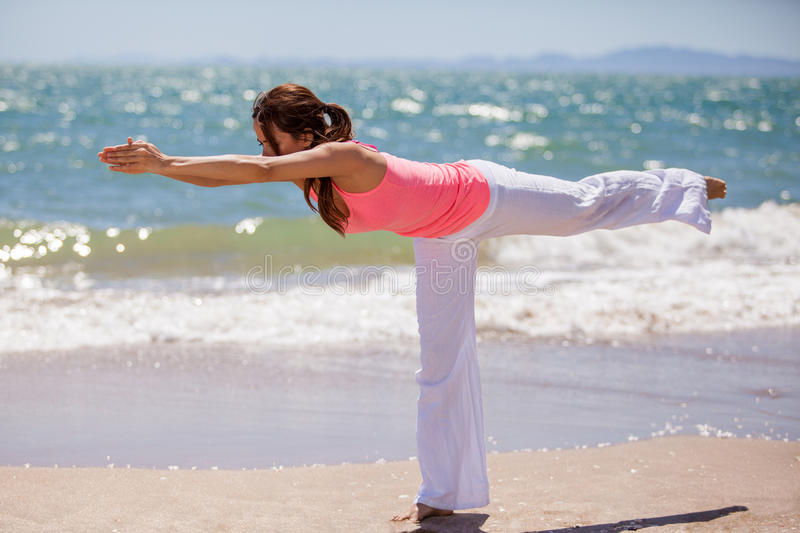 Yoga brings peace and balance. Cute young brunette maintaining balance for a yoga pose at the beach royalty free stock photo