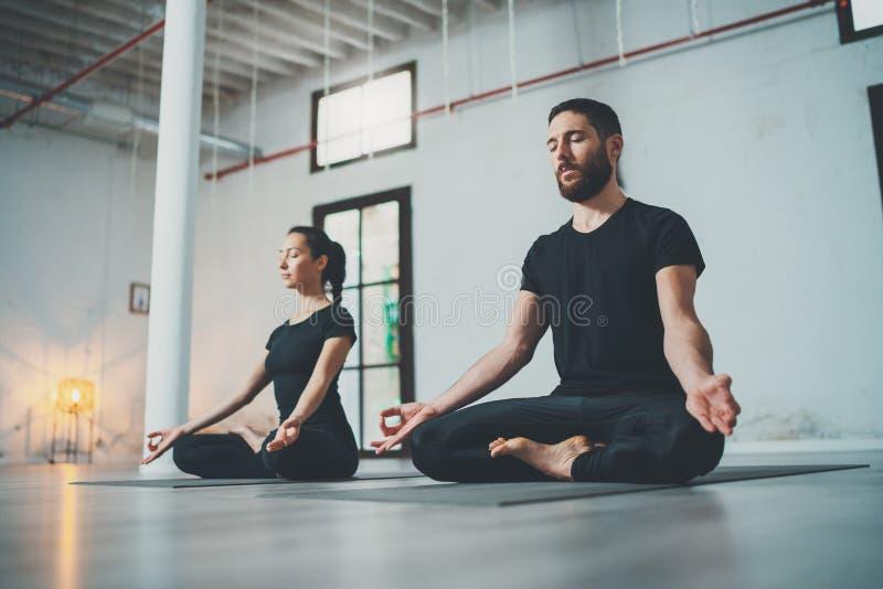 Yoga-?bungs-Klassen-Konzept Zwei schöne Leute, die Übungen tun ?bendes Yoga der jungen Frau und des Mannes zuhause lizenzfreies stockfoto