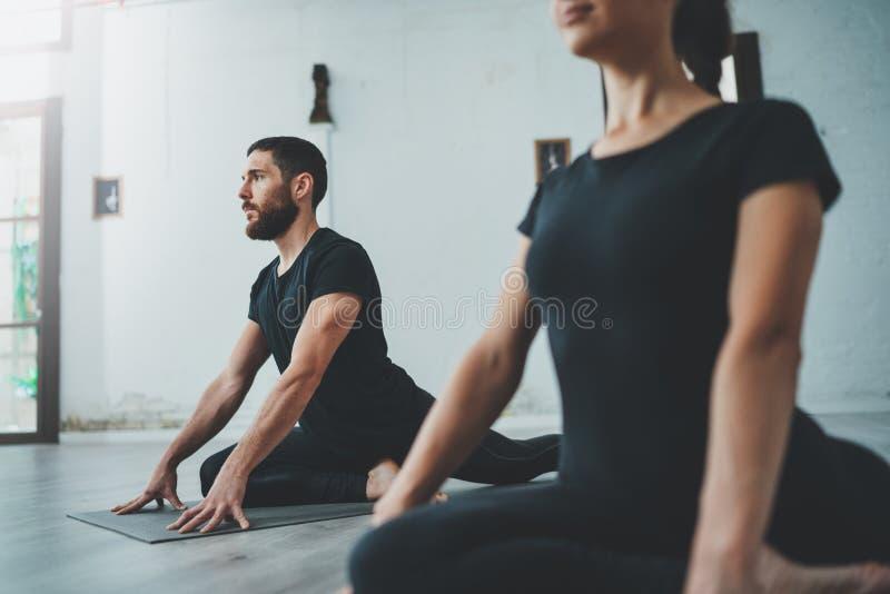 Yoga-?bungs-Klassen-Konzept Zwei schöne Leute, die Übungen tun ?bendes Yoga der jungen Frau und des Mannes zuhause stockfotos