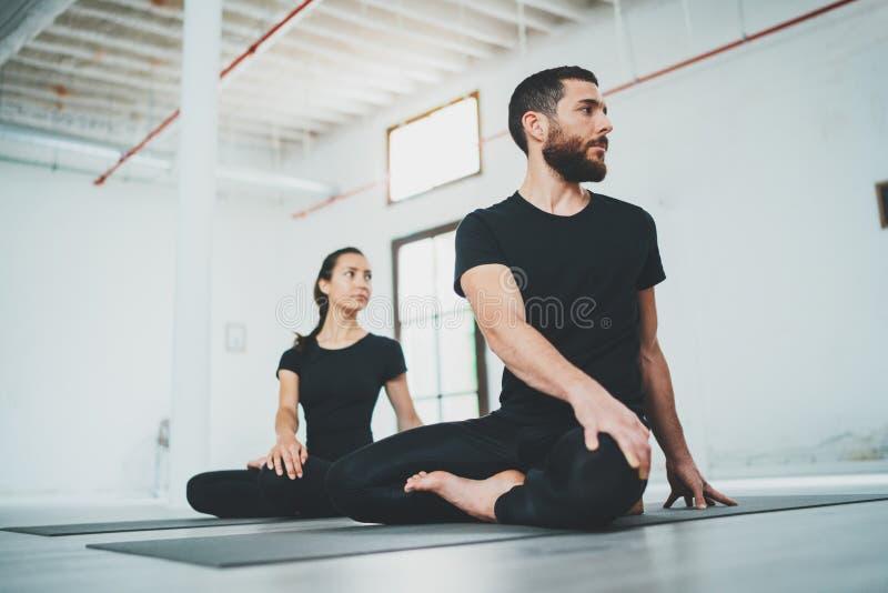 Yoga-?bungs-Klassen-Konzept Zwei schöne Leute, die Übungen tun ?bendes Yoga der jungen Frau und des Mannes zuhause stockbild