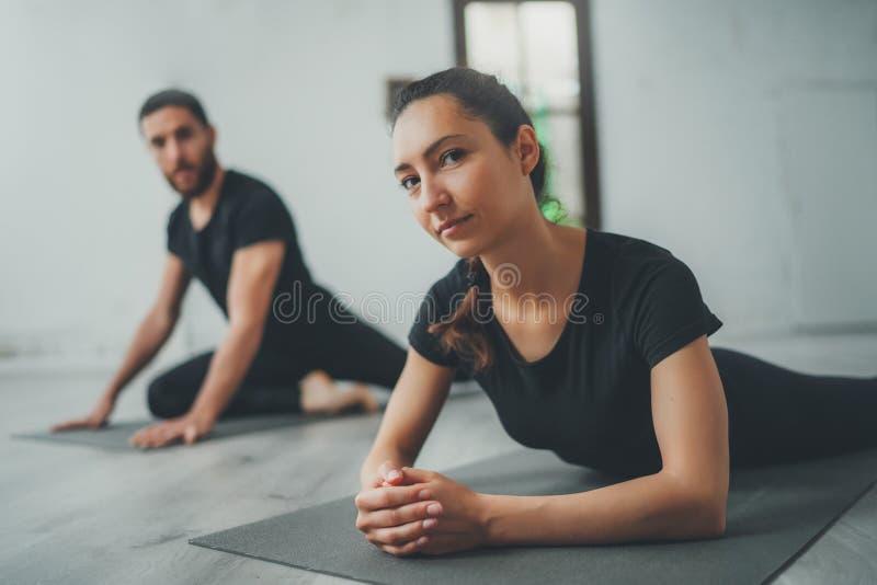 Yoga-?bungs-Klassen-Konzept Zwei schöne Leute, die Übungen tun ?bendes Yoga der jungen Frau und des Mannes zuhause lizenzfreie stockfotos